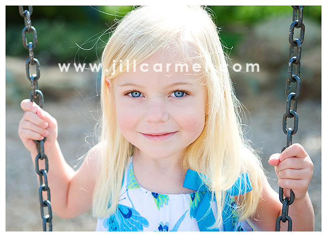 Natural light outdoor photo of a beautiful girl on a park swing.