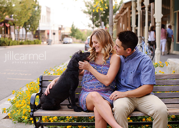 maternity portraits in Old Sacramento sitting on a bench with black dog