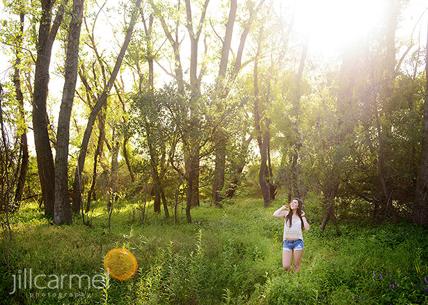 high school senior portrait in a green grassy field with lens flare
