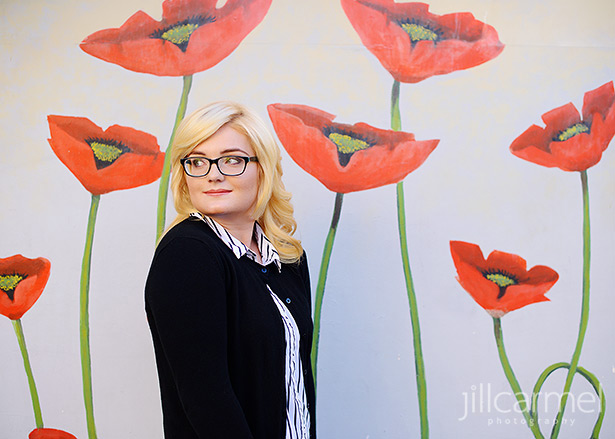 high school senior portrait in front of a wall painted with large red poppies