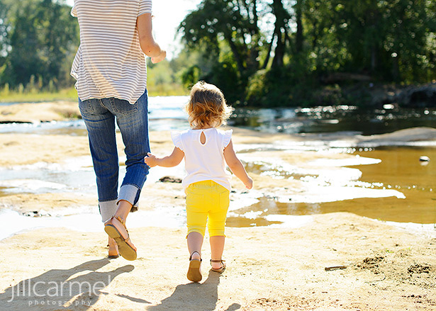 Little girl in yellow pants walking with mom along the American River