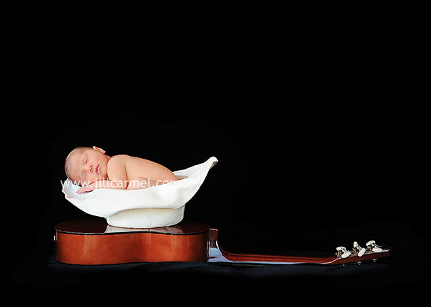 newborn baby in a cowboy hat for her pictures