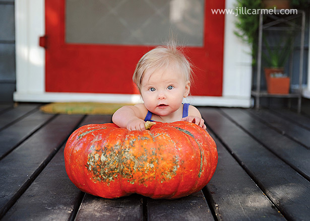 baby with big orange pumpkin for her portraits