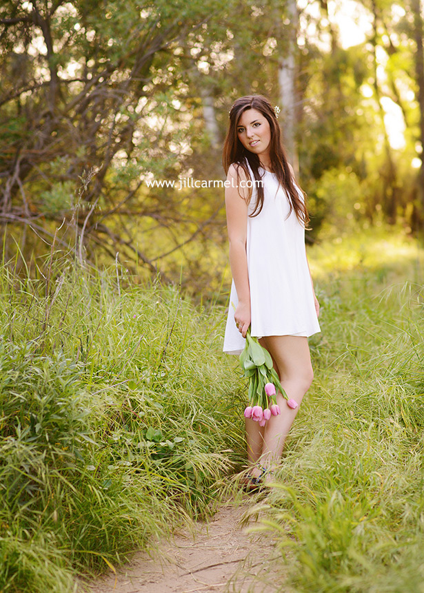 letting her flowers trail behind her in her natural graduation portraits