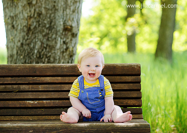 little boy in denim overalls sitting on a bench laughing