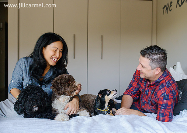 family laughs with their dog children on a bed