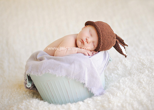 newborn baby sleeps in a blue bucket with a cute bunny ear hat