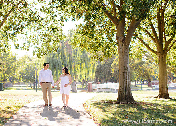 walking hand in hand through the trees for maternity photography in elk grove regional park