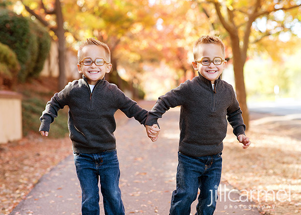 twin brothers run through the fall leaves