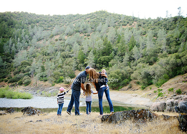 family kissing on the edge of the river overlooking the mountains