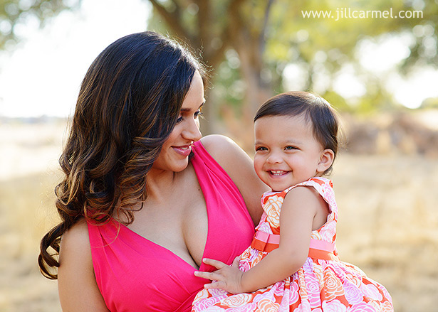 mom in pink dress with twin daughter smiling
