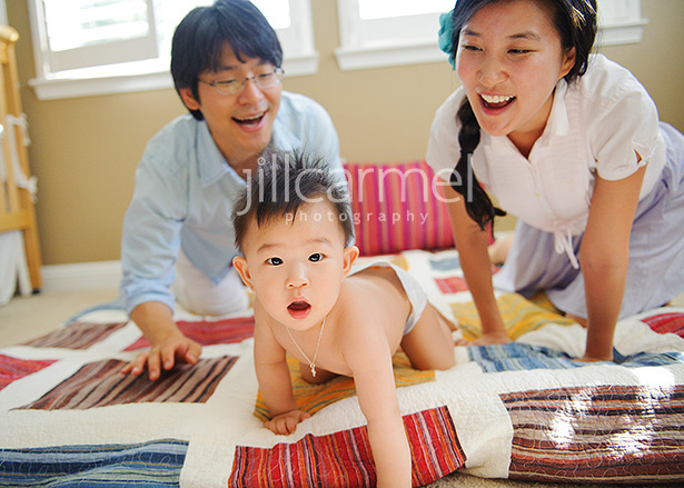 baby playing on the bed with mom and dad for these folsom home portraits