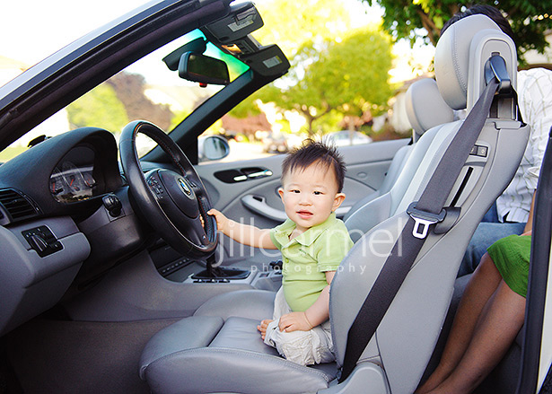 baby pretending to drive his dad's bmw m3 at their folsom home for his portraits
