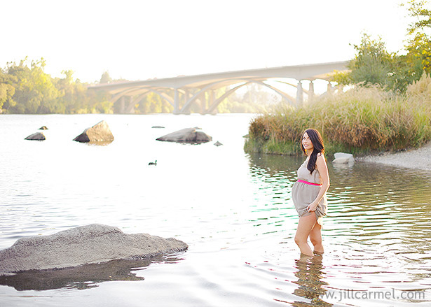 pregnant mom standing in the river with gray dress and bridge in the background