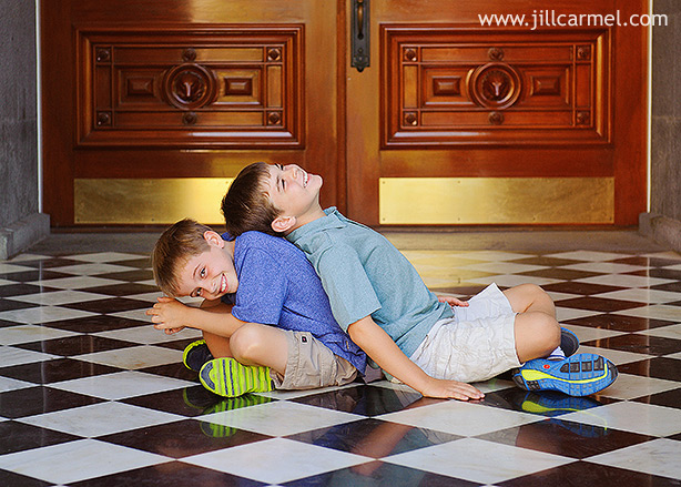 brothers wrestling on a black and white checkered floor in front of a big wood door