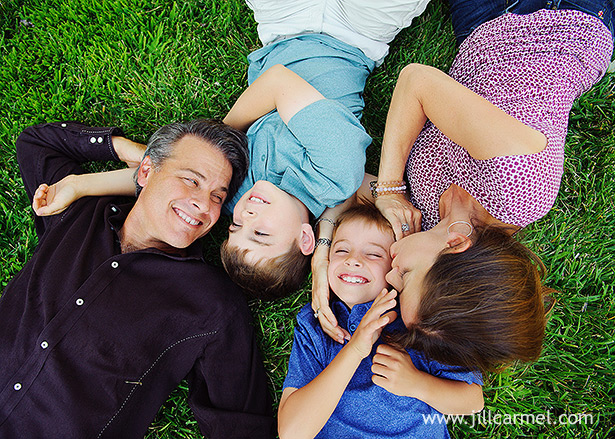 family cuddles and tickles in the grass with natural smiles