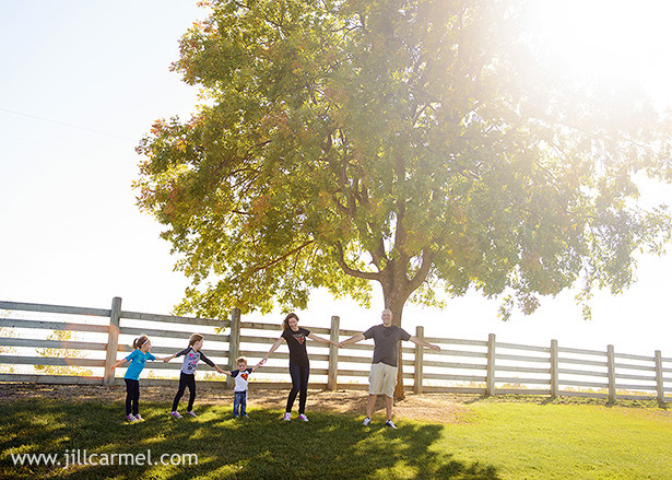 family holding hands and running down the hill at Gibson Ranch