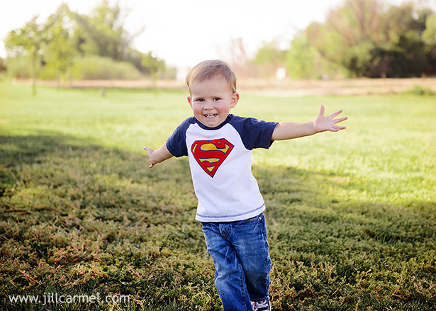 little boy flying around the Gibson Ranch field in his superman shirt