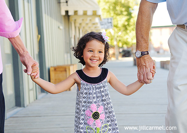 grandparents swing their granddaughter on a wooden walkway at old sacramento