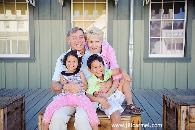 grandma grandpa and the grandkids smile big for their portrait