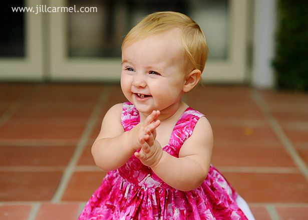little one year old girl claps with a smile while she stands in her pink dress