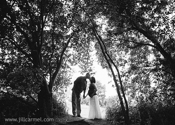 pregnancy portrait silhoutte kissing in the trees by the sacramento river pond