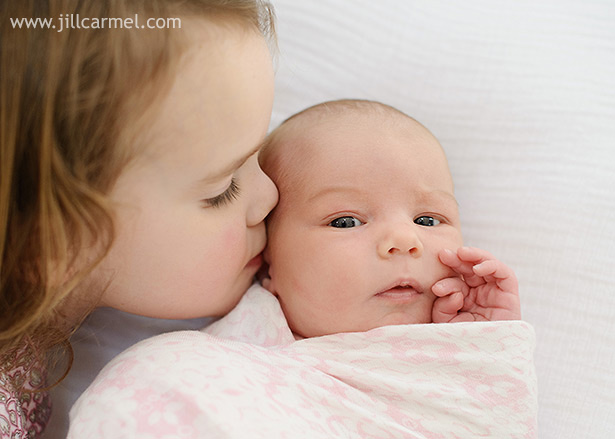 big sister gives kisses while little sister is wrapped in a pink swaddle | Jill Carmel