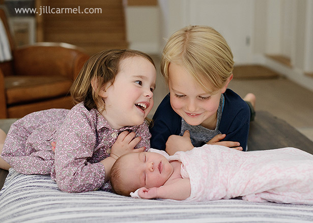 big brother and sister smile as they hold their little baby sister | Jill Carmel