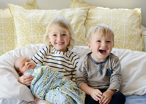 sister and brother are all laughs for this los angeles newborn photo shoot