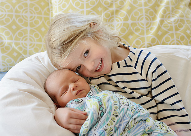 big sister holding her newborn brother striped dress against yellow patterned pillows