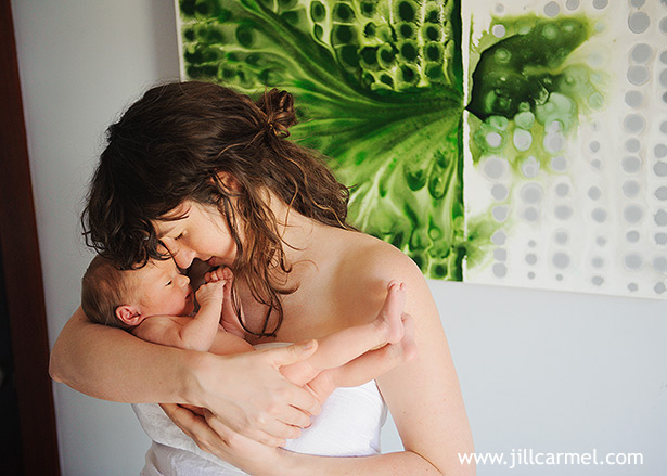 mommy kissing baby in front of luc schwab art piece