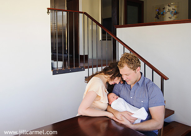 modern home with staircase and sunken dining room with mom and dan holding baby in los angelese