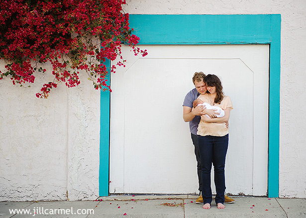 los angeles parents holding baby outside with turquoise frame and bouganvilla