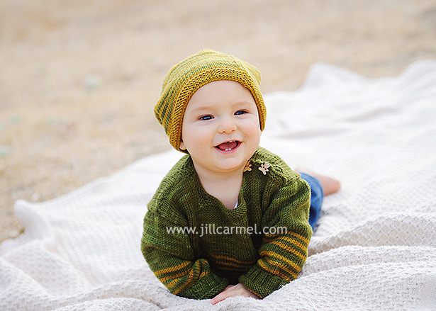 baby with knitted hat smiling at mom on the blanket