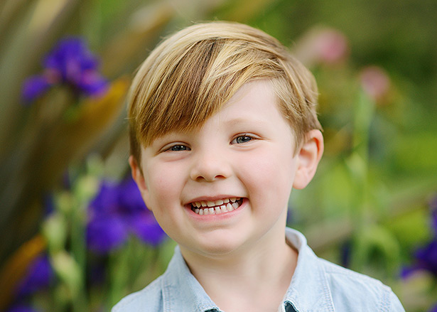 little boy smiles for pictures in front of the blue irises at Mckinley Park