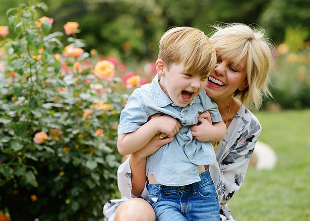 mom tickles her little boy in front of the roses at Mckinley Park for portraits