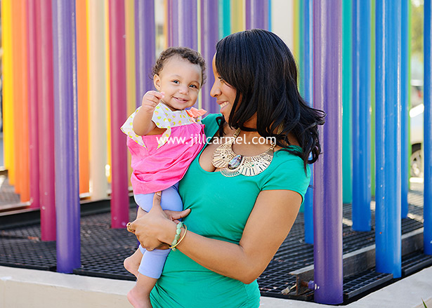mother and holding daughter in front of rainbow colors
