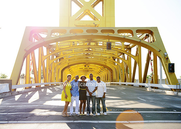 with the sun shining behind them, the family poses for their picture in front of the bridge