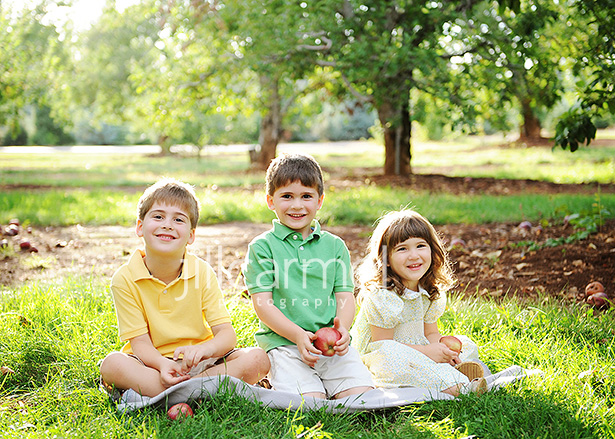 brothers and sister sitting in the sun for their outdoor photographs