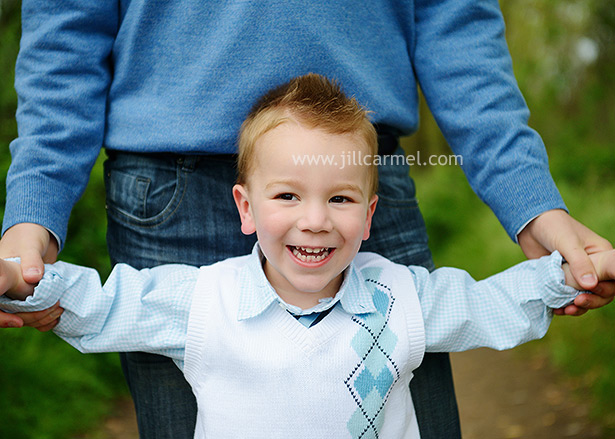 big brother laughing while daddy lifts him up in the air for their spring session