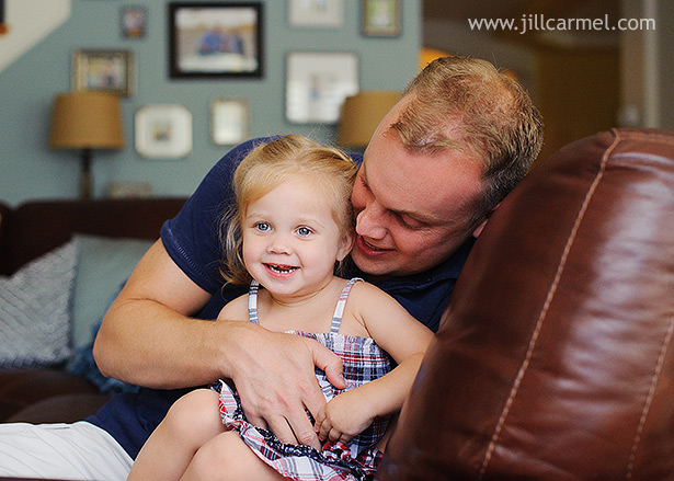 big sister getting tickled by daddy on the sofa