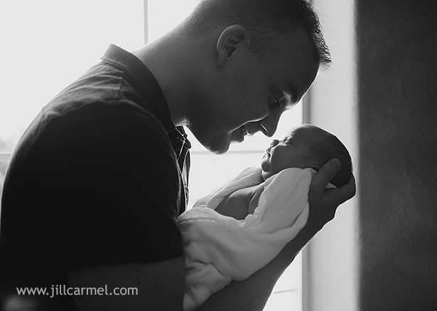 sweet moment between daddy and his new baby girl in front of the window