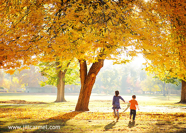 brother and sister holding hands and running through the autumn trees
