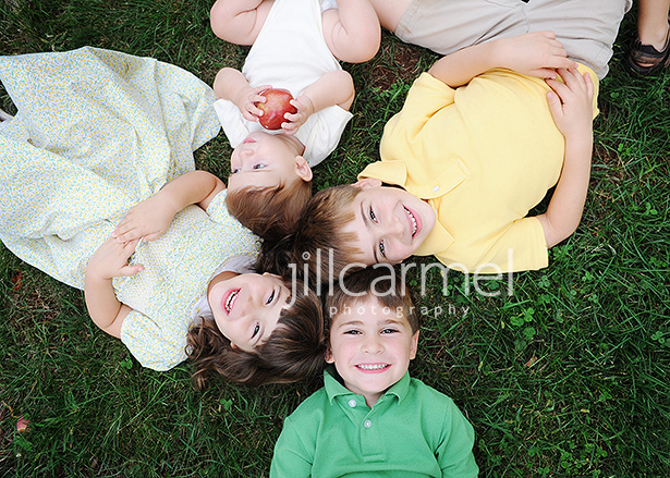 everyone lying on the grass with natural smiles for their pictures