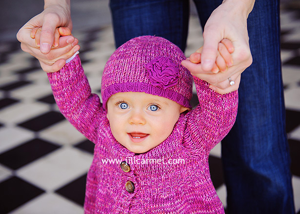 baby daughter dressed in pink with a knit hat playing on a checkered floor in sacramento