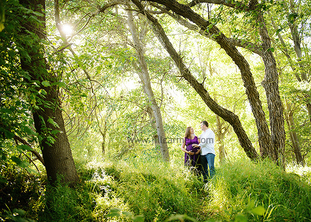 posing in the forest for their maternity session with the sun coming through the trees