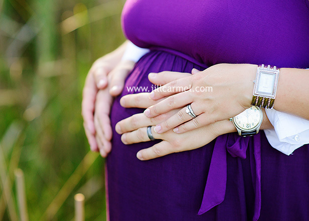 showing off their wedding rings on mommy's belly for their maternity session