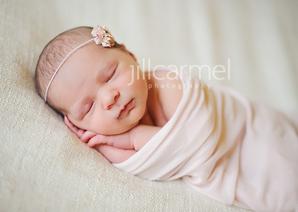 cozy baby with pink flower headband and wrapped in gauze in sacramento