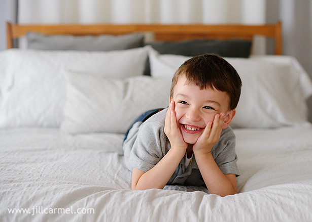 sweet smiles from brother hanging out on the bed