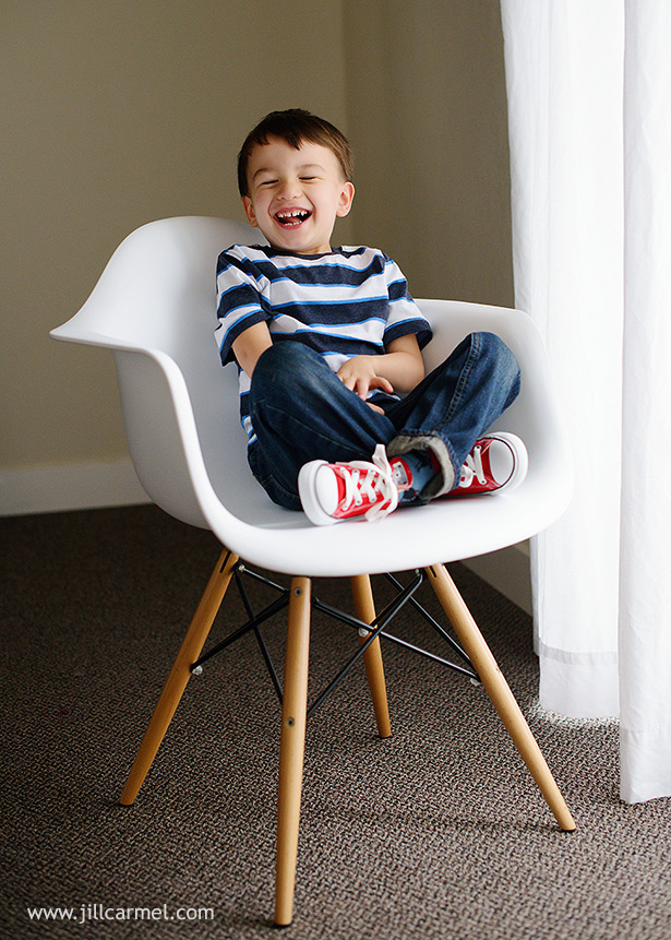 little boy laughing red converse in modern eames chair